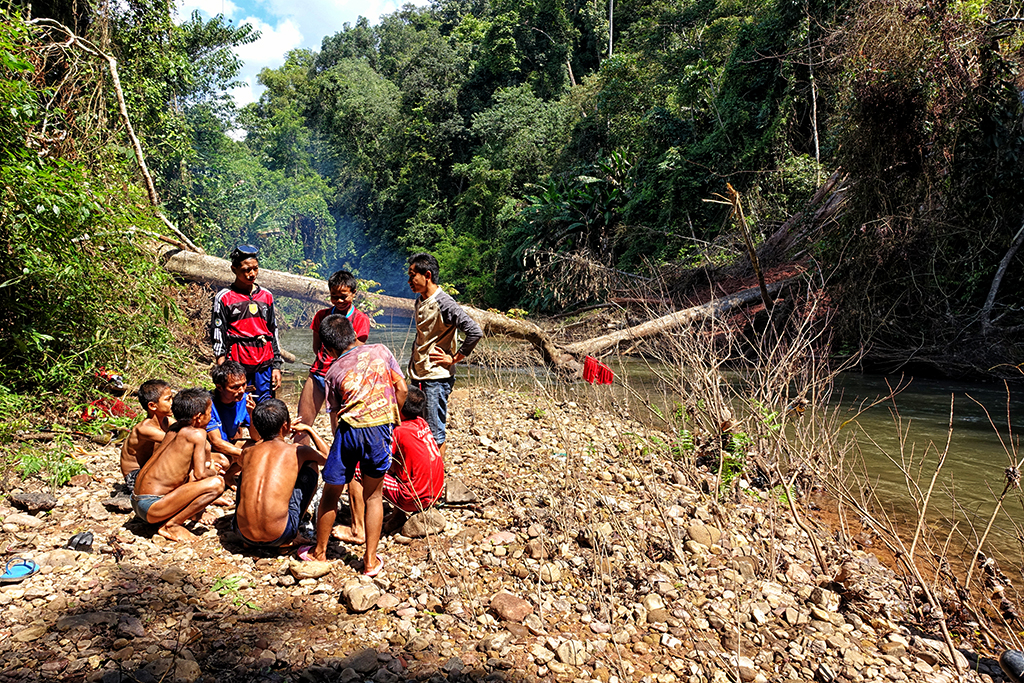 Local kids making fire and fishing in Nam Ha NP in Northern Laos.