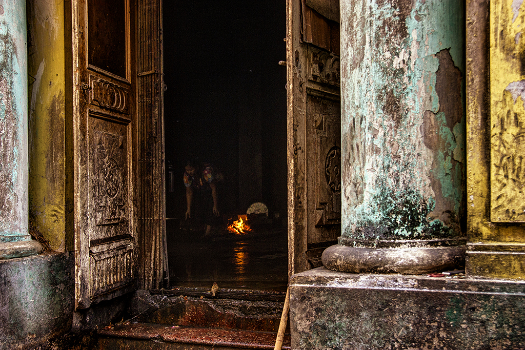 Making fire inside the old British colonial building in Yangon, Burma