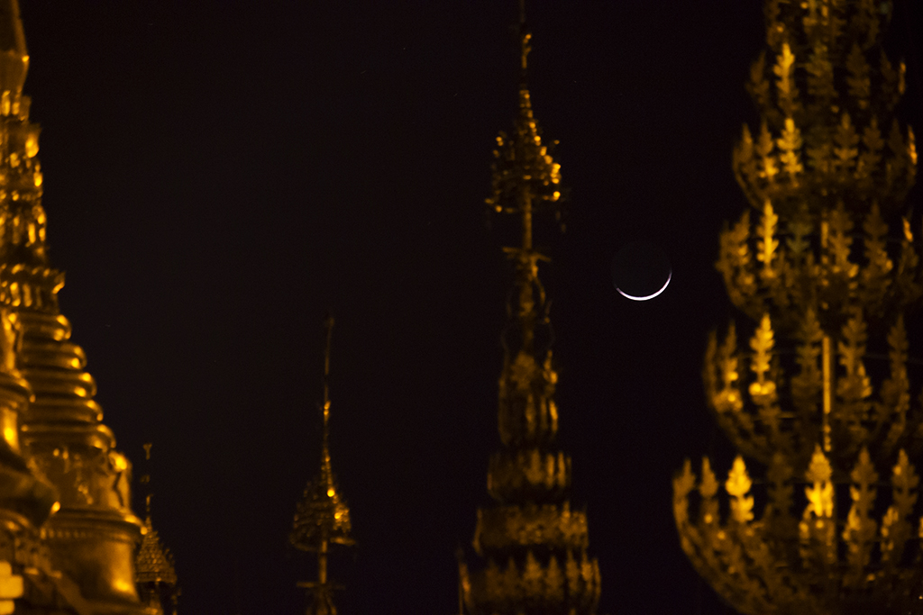 A dissapearing moon shines through the golden pagados of Shwedagon, Myanmar.