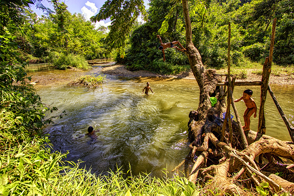 Kids playing, washing and swimming outside the hiding cave outside Nong Khiaw, Laos