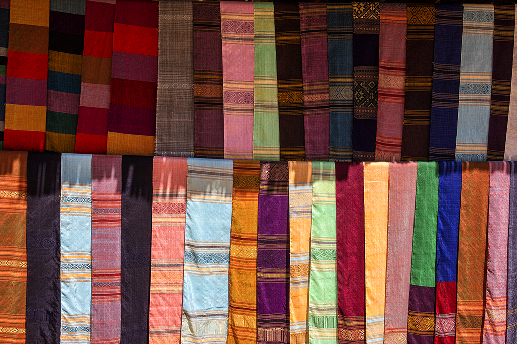 Silk and cotton weaving outside huts in Ban Sop Jam along the Nam Ou river in Northern Laos.